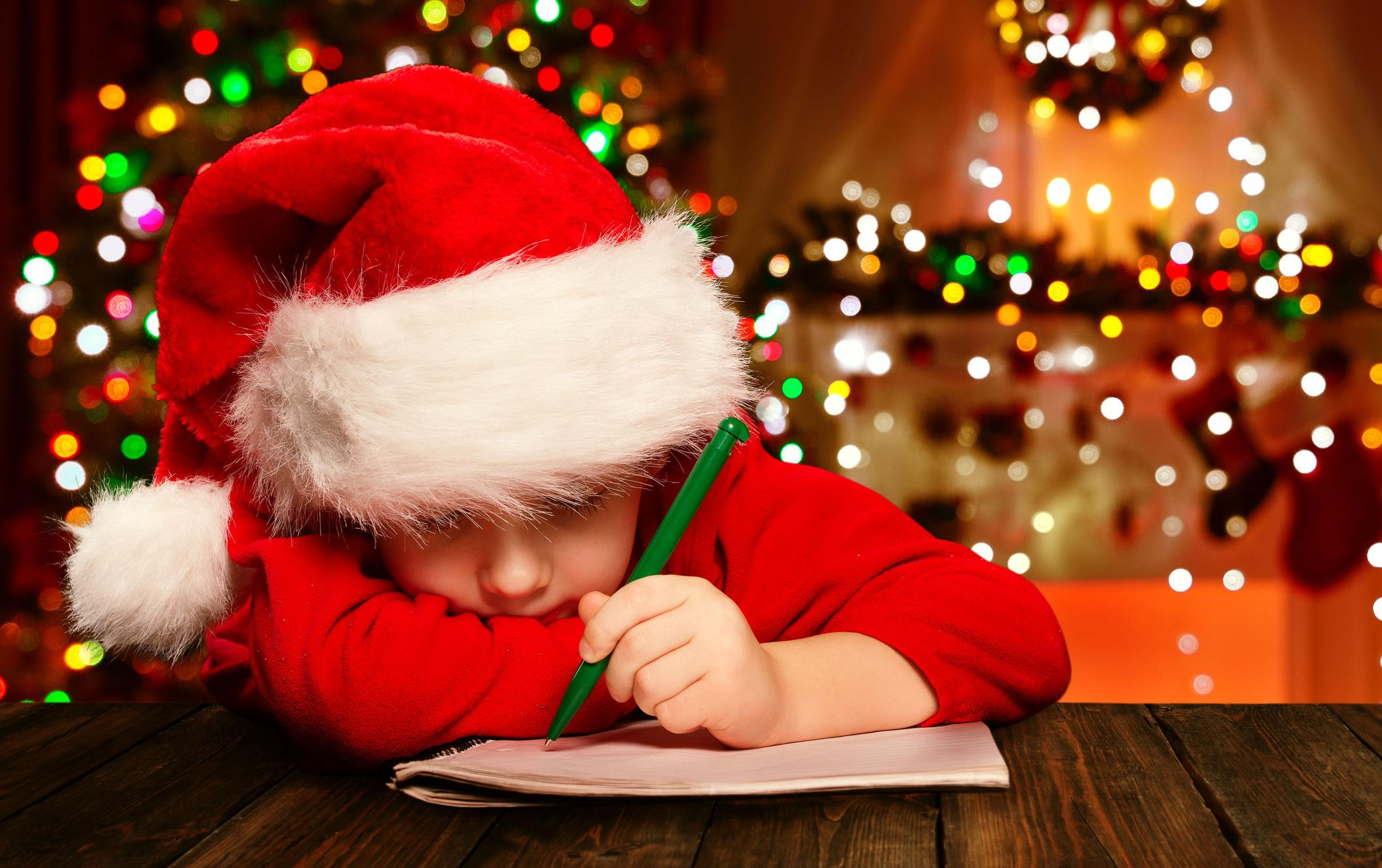 Child wearing Santa hat sits at a table writing on a tablet, Christmas lights in the background