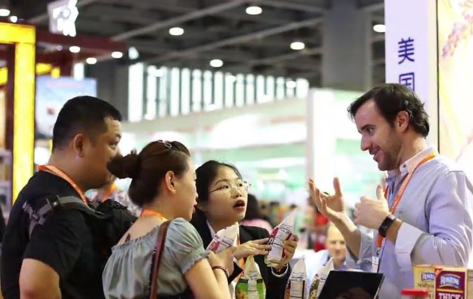 People gather around a booth at a trade seminar holding rice products
