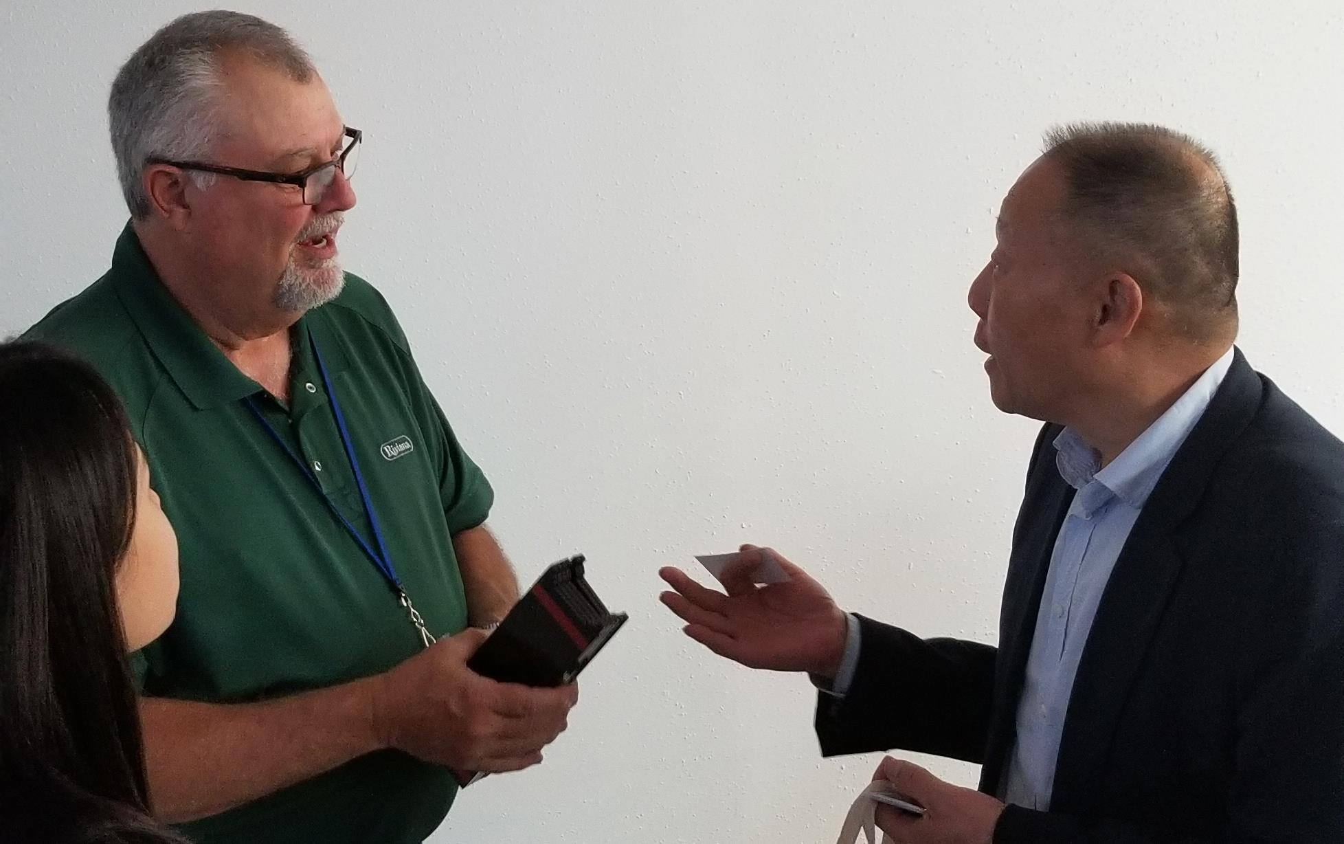 Two men stand face-to-face exchanging gifts and business cards, person recording video on cellphone in foreground