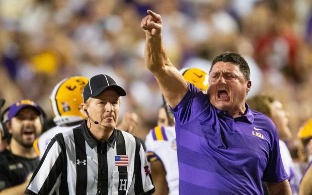 LSU Coach Ed Orgeron gets animated, referee stands nearby