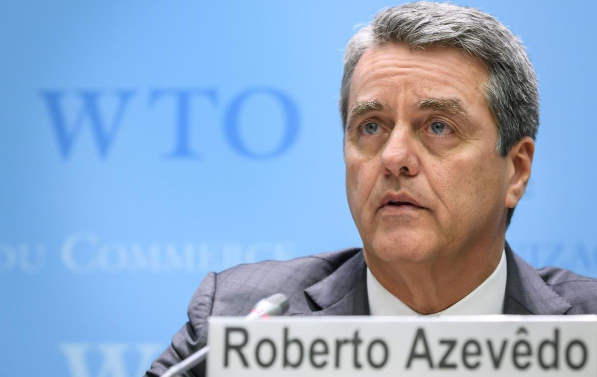 """WTO Director General Roberto Azevedo sits at table with name plate and """"WTO"""" on wall in background"""