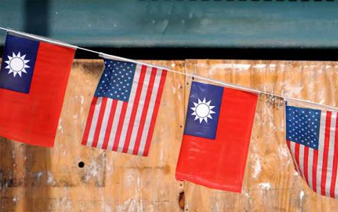 US and Taiwan flags fly on string in front of wooden board