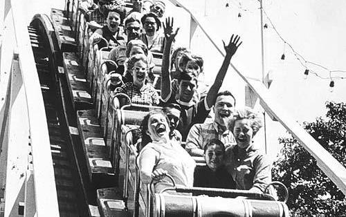 B/W photo of people riding on a wooden roller coaster