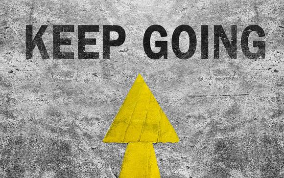 "Black tennis shoes with white laces standing on yellow arrow pointed at text ""Keep Going"""