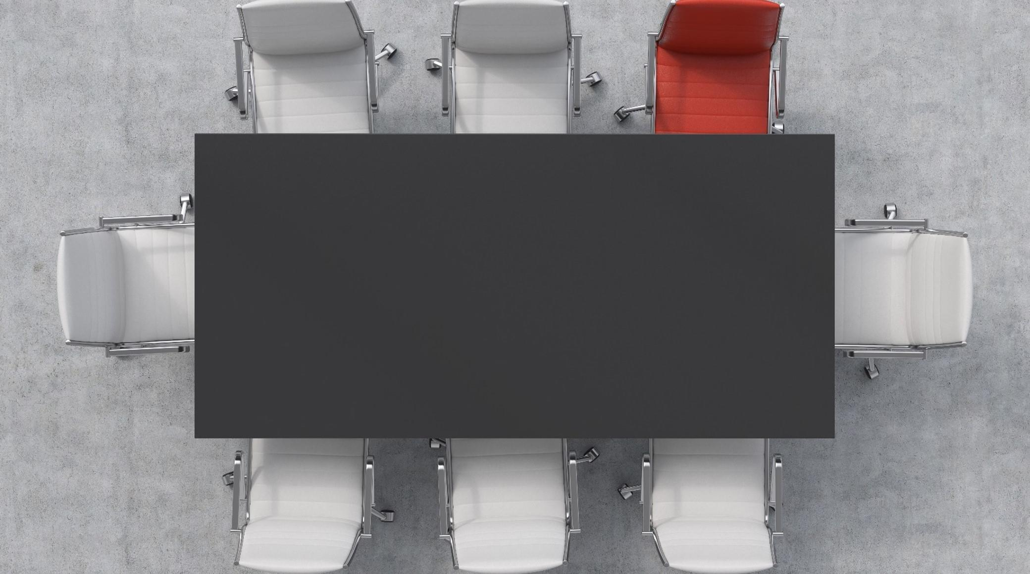Aerial view of rectangular black table surrounded by white chairs plus one red chair