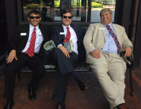 Three men wearing sunglasses and suits sitting on a bench