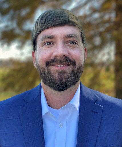 Tim Huggins, headshot, white man with brown hair and beard wearing white shirt and blue jacket