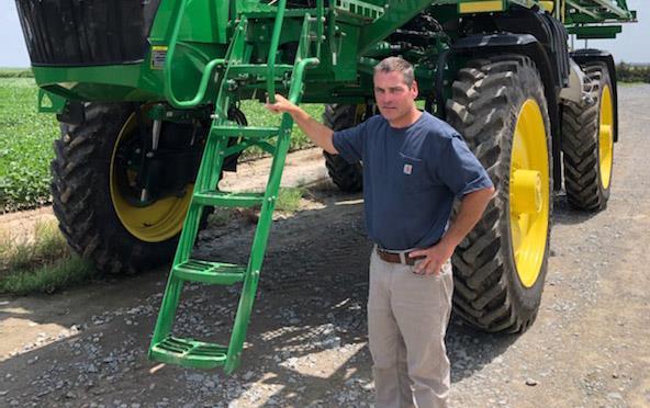 Man holds onto ladder of green pesticide sprayer