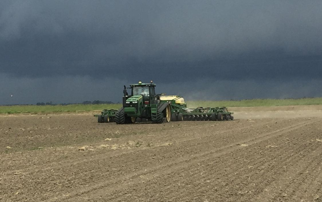 Green combine planting in dirt field, ominous dark storm clouds overhead