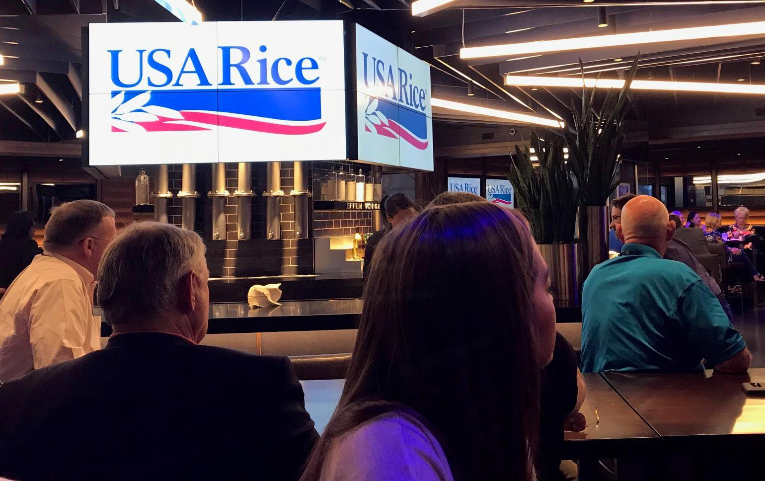 Group of people seated with backs to the camera in a large meeting room, USA Rice text and logo illuminated on big screens