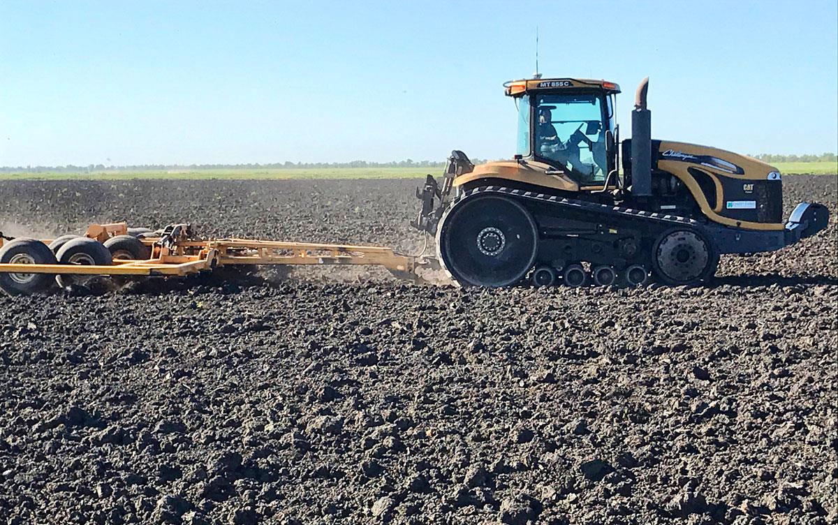 Yellow tractor in field of fresh dirt