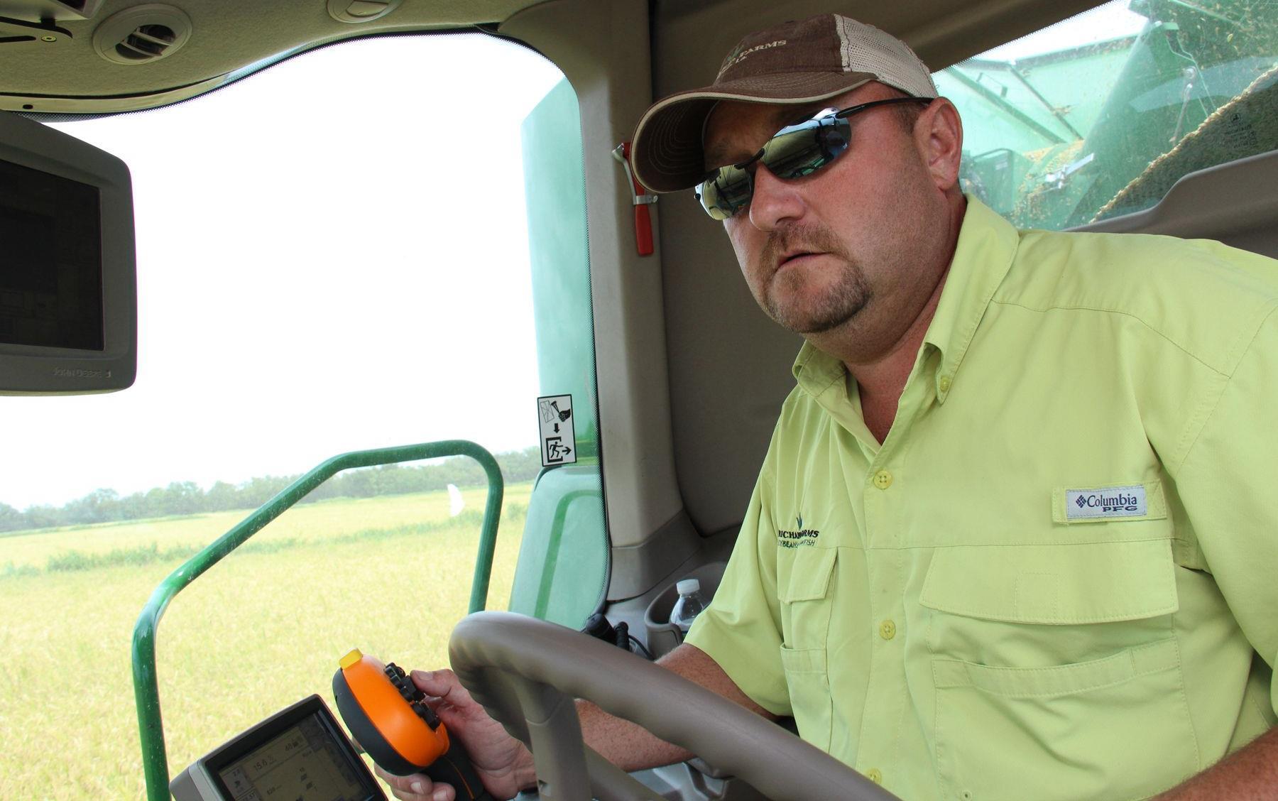 Man wearing yellow shirt and sunglasses drives green combine