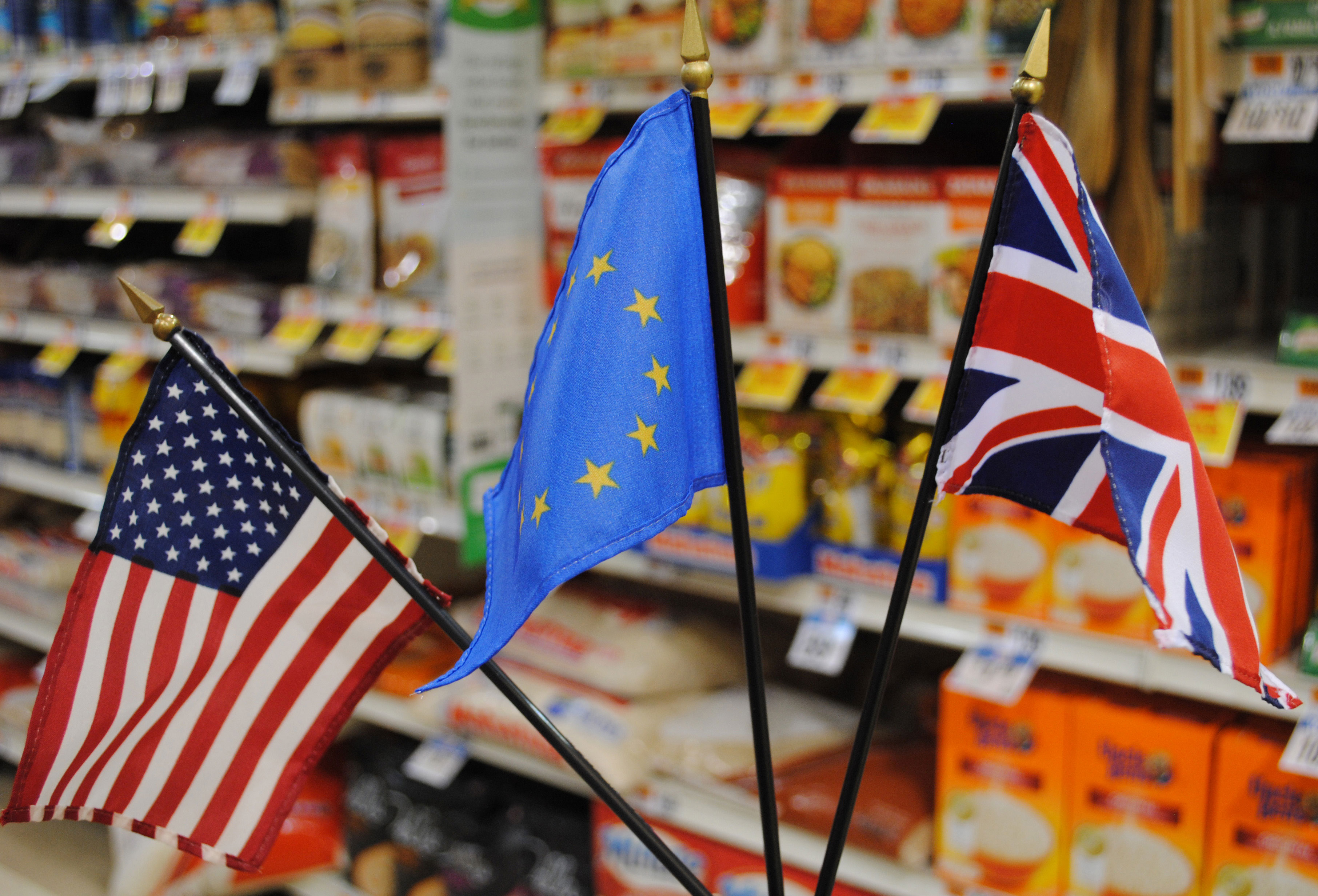 Image of three flags - U.S., EU & UK - in front of supermarket rice aisle