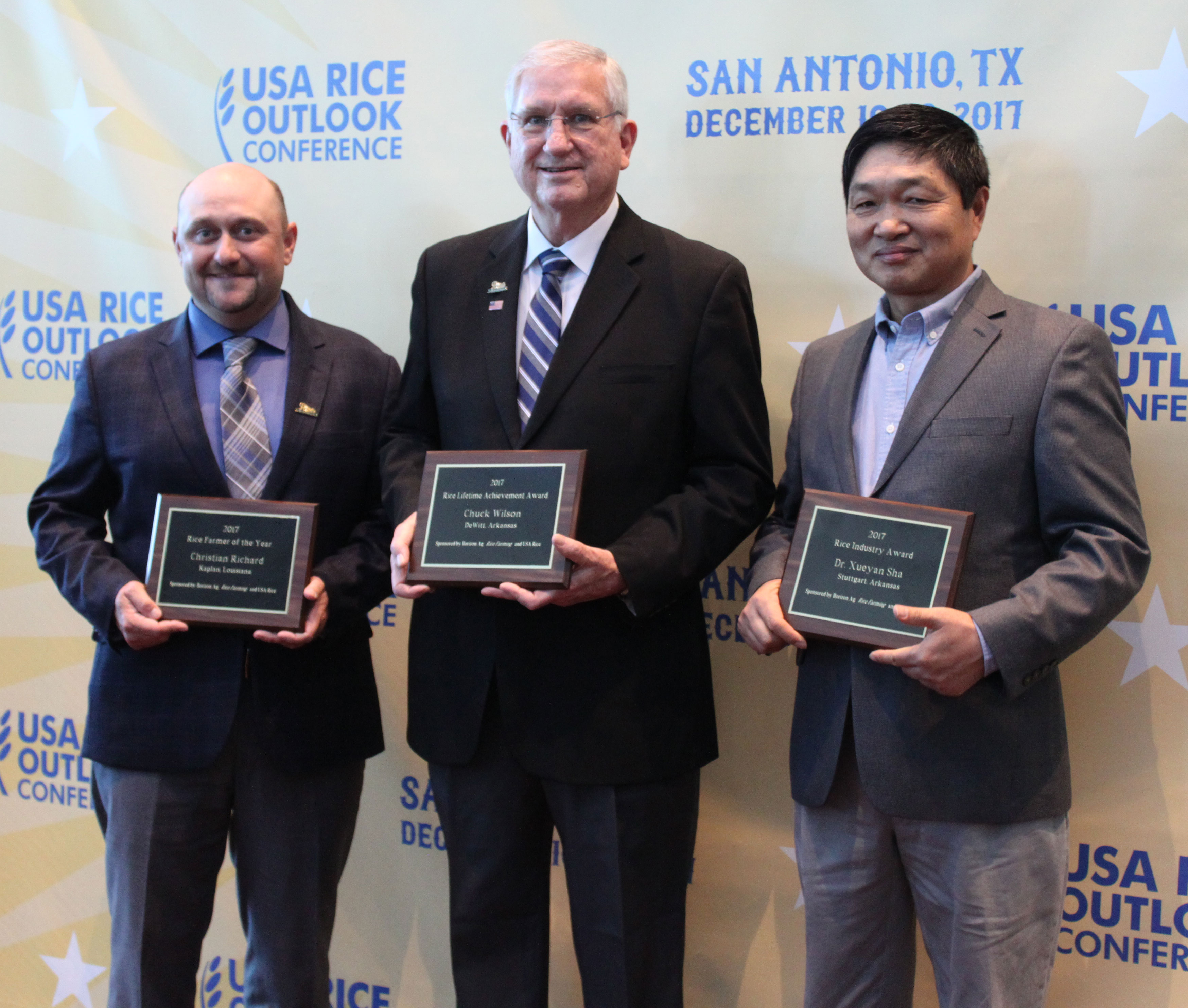 2017 Rice-Awards recipients holding plaques, standing in front of Outlook step-and-repeat