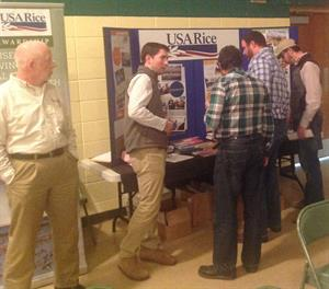 2016-mo-rice-conference, group of men stand around USA Rice booth
