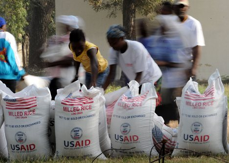 Image of people picking up bags of U.S. rice from food aid shipment