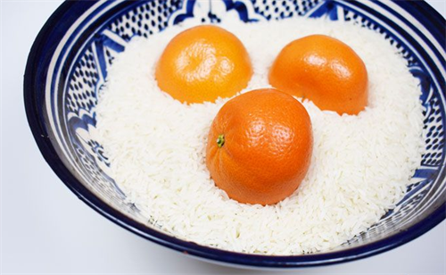 Close up view of three clementines  in a bowl of raw rice.