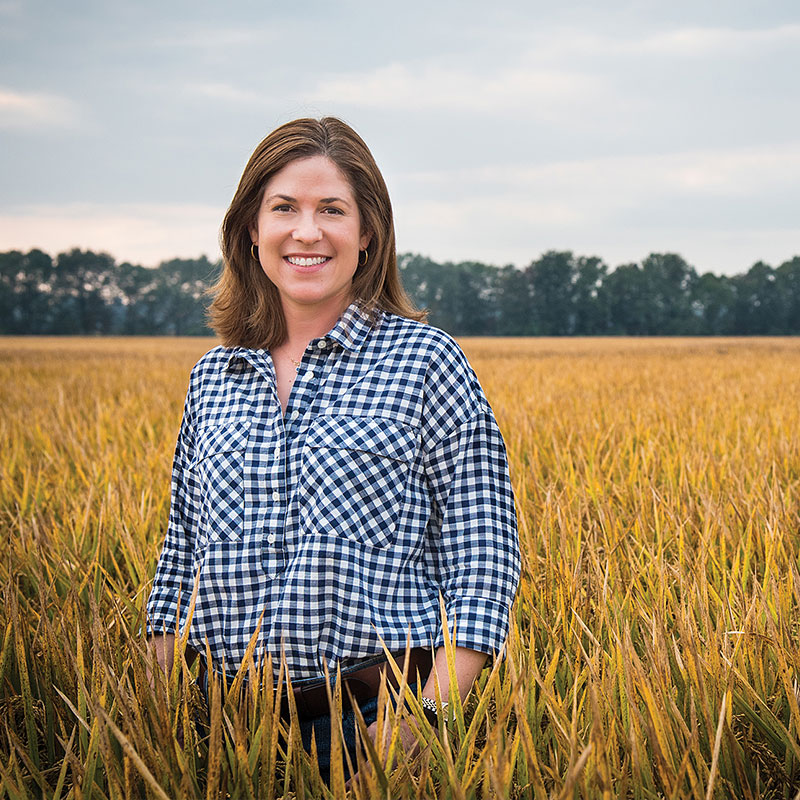 Rice farmer, Jennifer James, standing in a rice field.