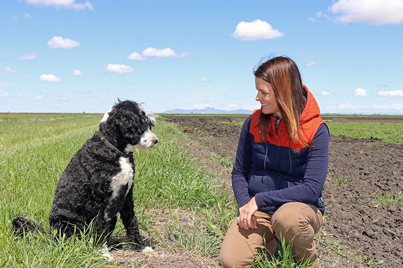 Kim Gallagher with her dog Comet in a field with blue sky.