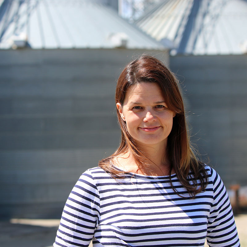 Rice farmer Kim Gallagher in front on grain bins.