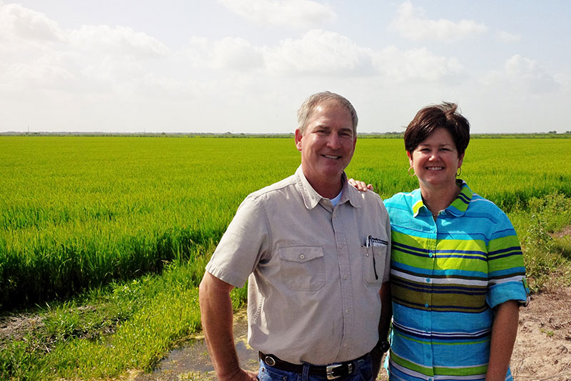Linda and LG Raun in front of a rice field.