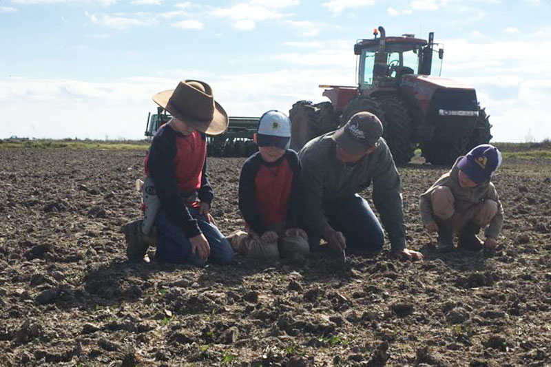 Paul Johnson examining soil in a field with his children.