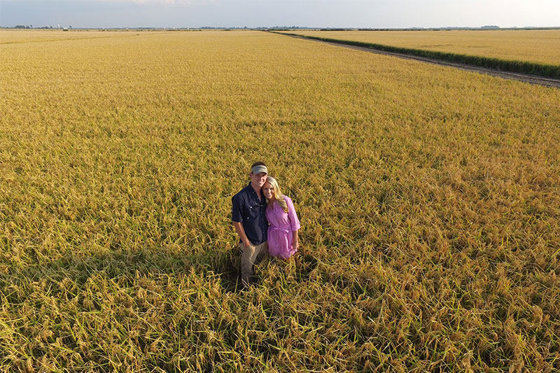 Rice farmer Ryan Sullivan standing in a rice field with his wife.