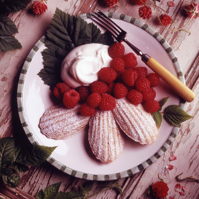 Almond rice madeleines on white plate with raspberries