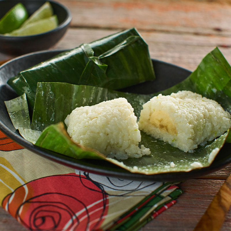 Banana Sticky Rice cut in half and displayed on an open banana leaf.