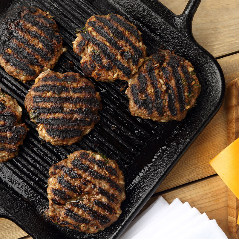 Overhead image of a skillet with 6 grilled hamburger patties.