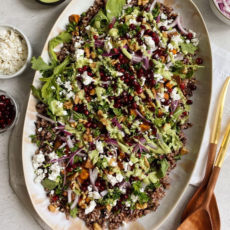 Overhead view of a platter of Black & Wild Rice Salad with Sweet Potatoes & Tahini sauce.