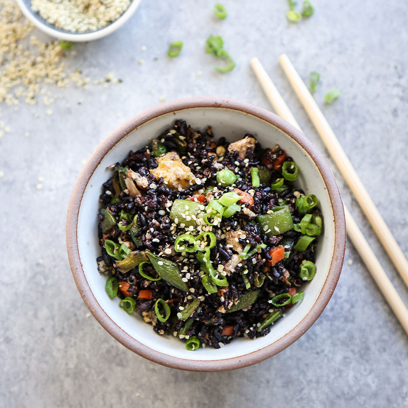 Overhead shot of Black Fried Rice with Snap Peas in a white bowl.