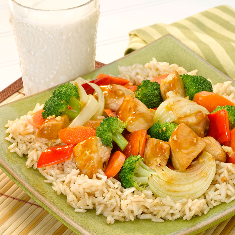 Side view of brown rice with chicken and vegetables on a green plate.