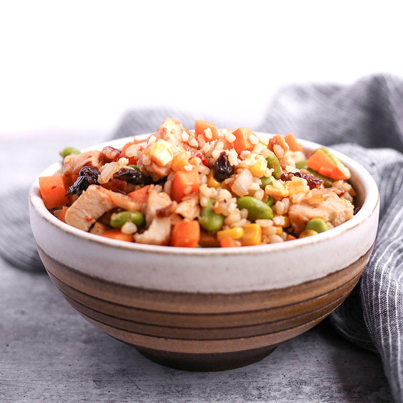 Side view of brown rice and sweet potato hash in a bowl.