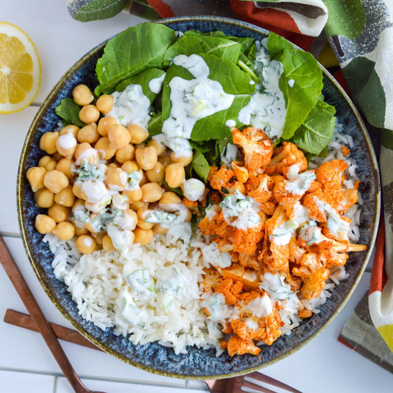 Overhead view of buffalo-cauliflower rice in a bowl with lemon on the side.