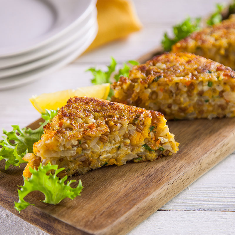 Side view of butternut squash cakes on a wooden serving platter.