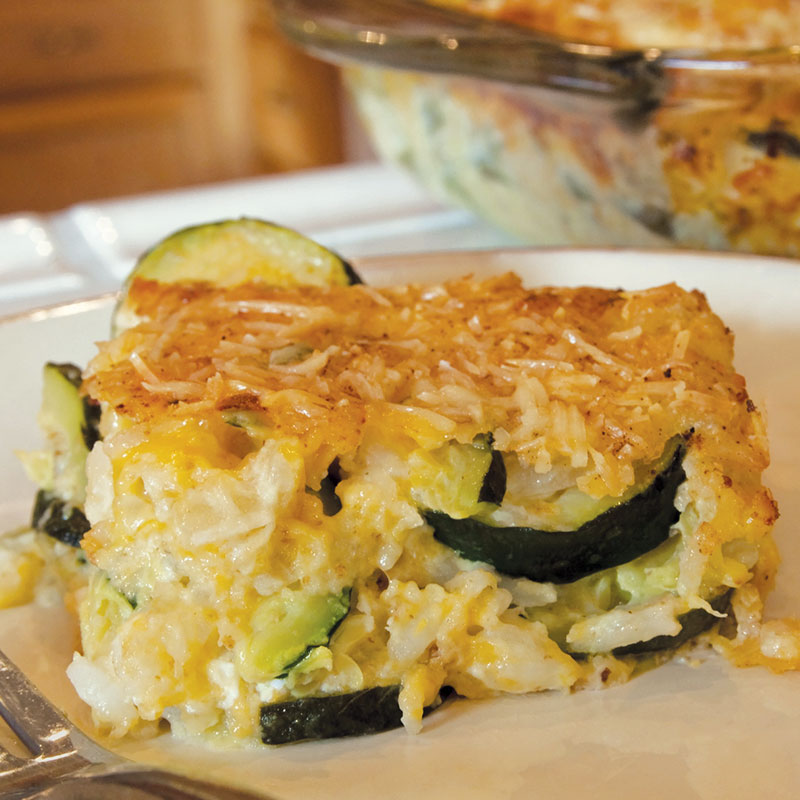 Side view of California rice and zucchini casserole on a white plate.