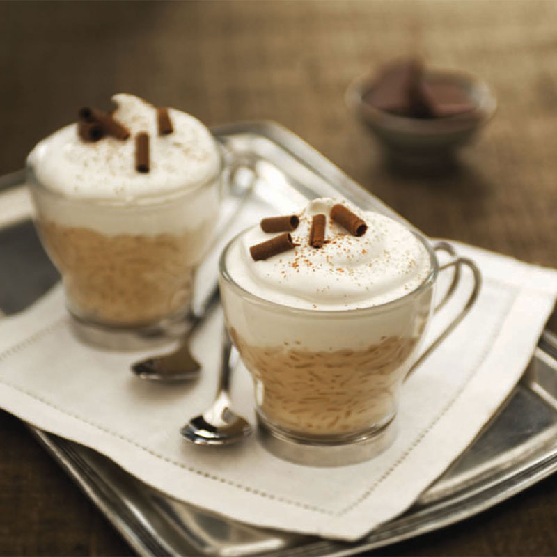 Two Cappuccino Rice Pudding Cups in glasses and topped with whipped cream.