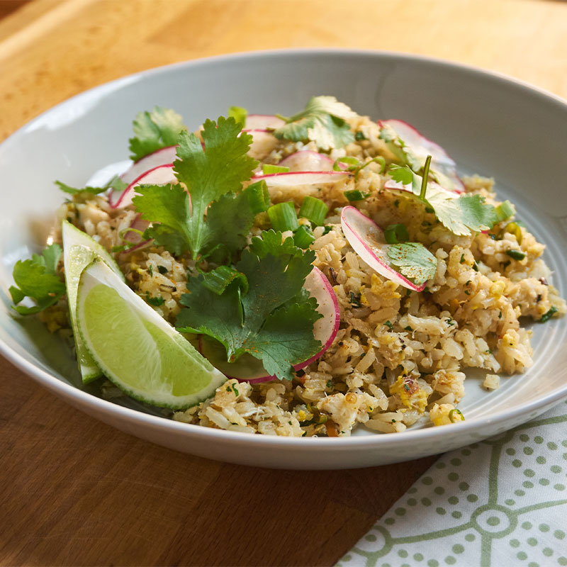 Overhead shot of crab fried rice in a white dish with lime wedges, garnish, and a radish slices.