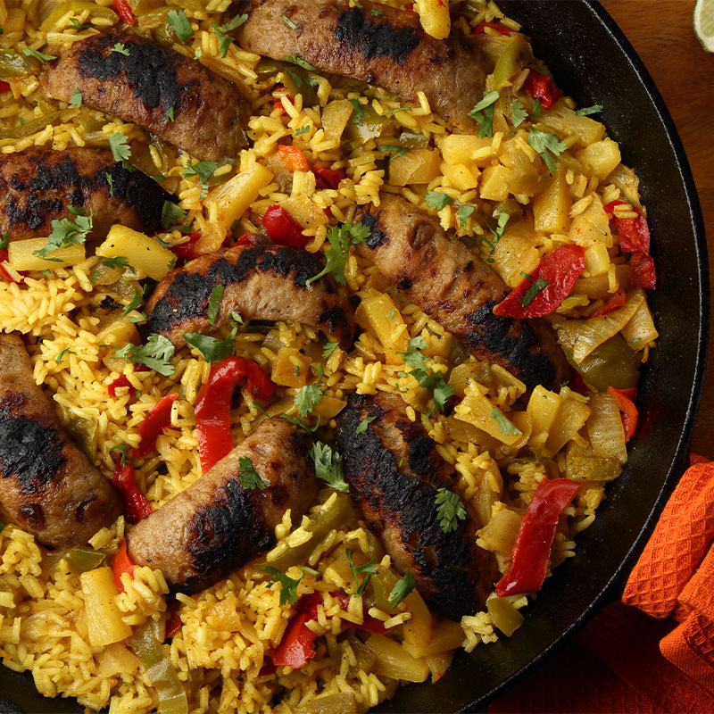 A skillet full of chicken-apple sausage and yellow rice with pineapple chunks and peppers.