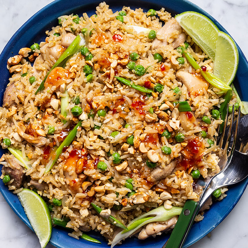 Overhead view of chicken green onion fried rice on a blue plate with lime wedges.