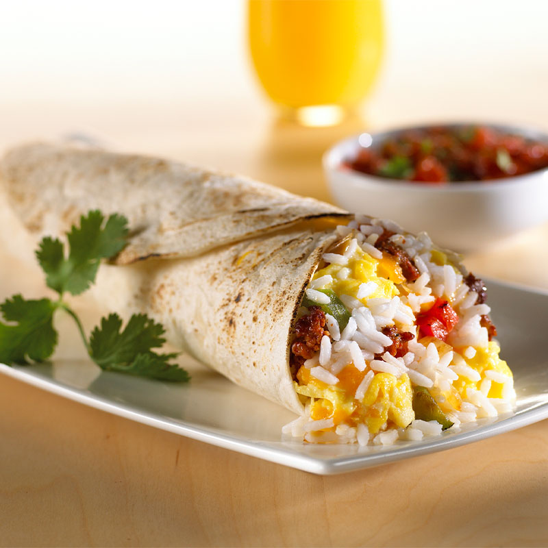 Side view of one Chorizo, Rice & Egg Wrap on a white plate.