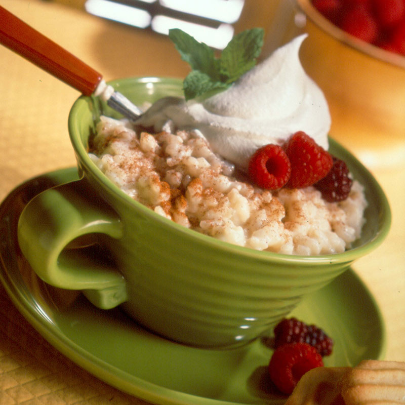 Side view of cinnamon rice pudding in a green mug topped with whipped cream and berries.