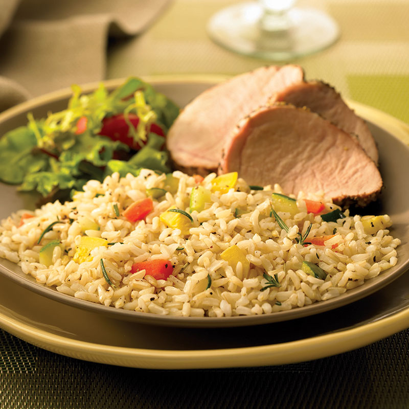 Side view of confetti rice pilaf on a plate with sliced ham and salad greens.