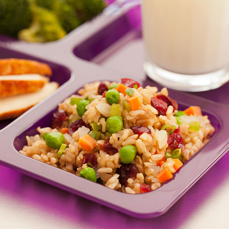 Close up view of cranberry brown rice with veggies on a purple school lunch tray.
