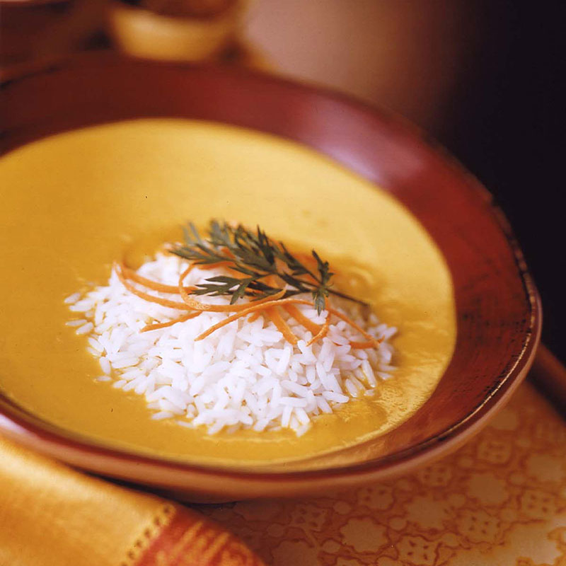 Overhead shot of creamy curry carrot soup with a serving of rice on top.