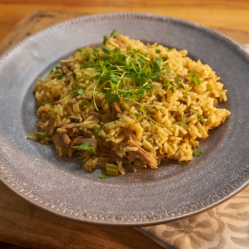 Side view of dirty duck rice in a grey bowl.