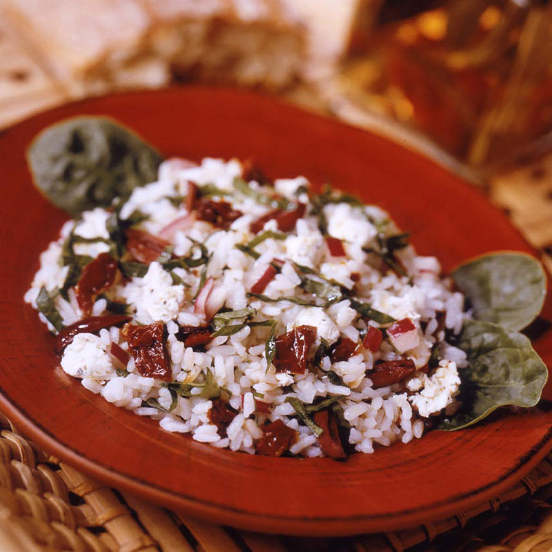 Side overhead shot of Greek Garden Rice Salad in a red bowl.