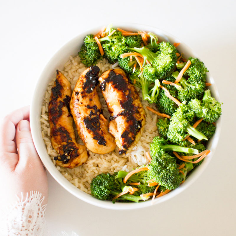 Overhead view of grilled chicken and veggie rice bowl.