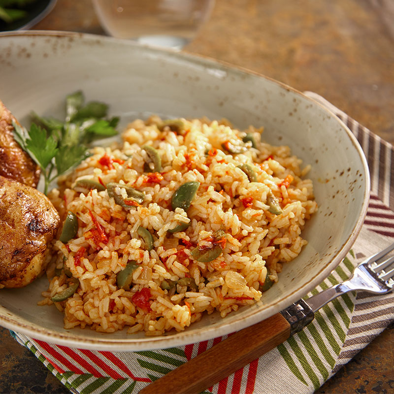 Side view of harissa mixed rice with chicken on a cream plate.